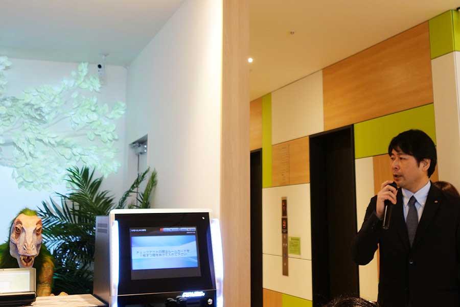 「H.I.S.ホテルホールディングス」の取締役・小高峰浩二さん。左側に見えるのは恐竜のロボット