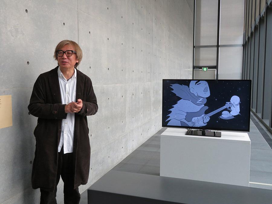 新作アニメ作品《地蔵マンZ》について解説するしりあがり寿。展覧会の末尾で見られる