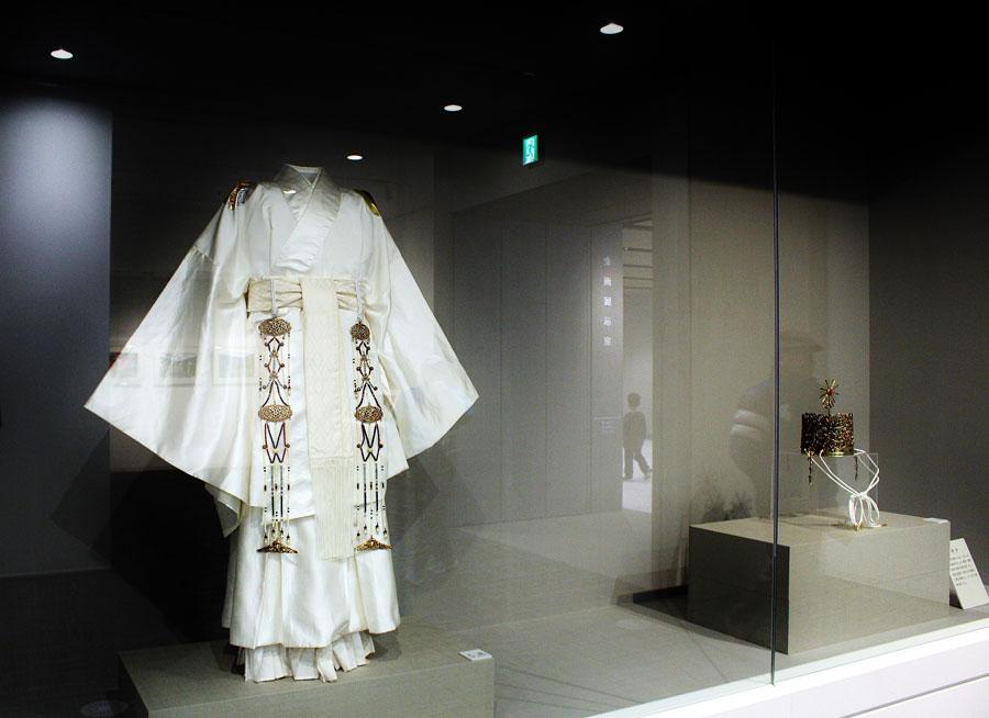 左の礼服(らいふく)は、天皇の服としての象徴である「日」「月」を肩に、背中の襟下に「北斗七星」を装飾。右の礼冠(らいかん)は、唐草文様の冠に太陽と雲を象徴した飾りが付き、宝石がちりばめられる