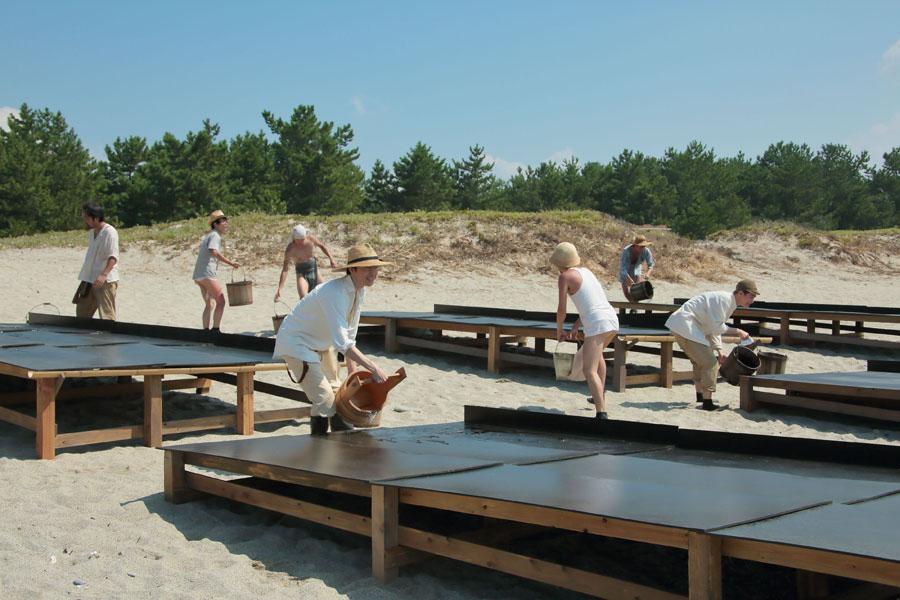 泉大津の海岸で従業員たちと一緒に塩作りをしている萬平(中央・長谷川博己)