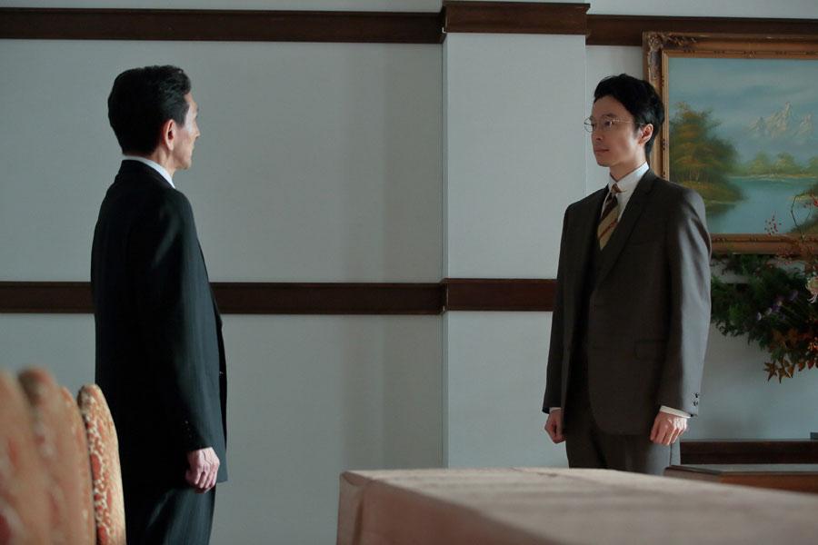 梅田銀行の会議室で担当の矢野(左・矢島健一)に対して不義理を詫び、「でも池田信用組合の、池田という町の将来に関わる大事な話です。どうかご理解ください」と言う萬平(長谷川博己)