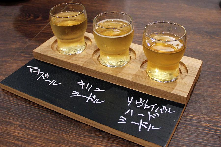 ハーフサイズの150mlグラスで提供される「樽生シードル日替わり飲み比べセット」(3種980円)。