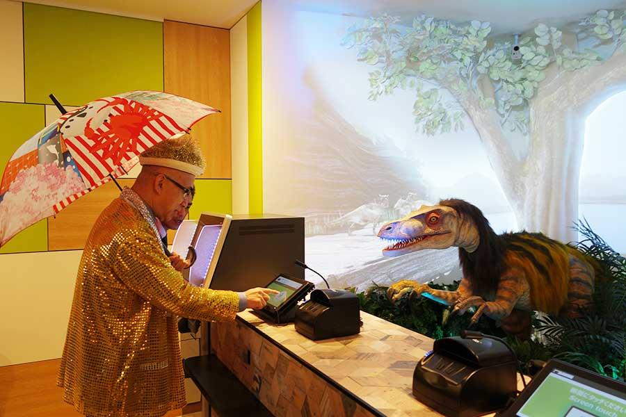 「大阪観光局」理事長の溝畑宏さんが、恐竜型ロボットに向かって名前を伝えてチェックイン