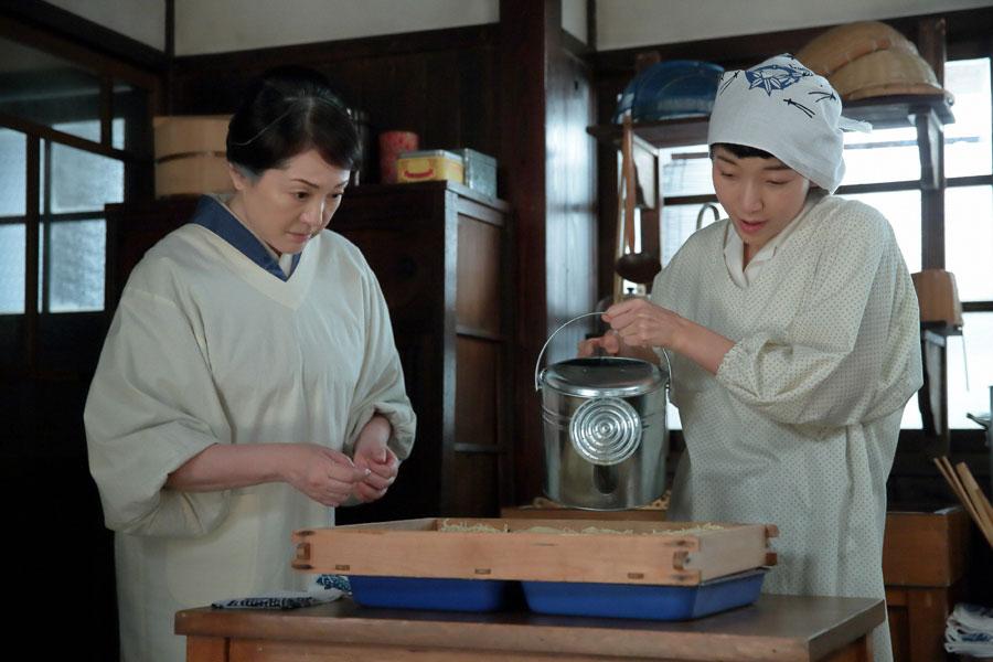 鈴(松坂慶子)にラーメンの作り方を説明し、麺にスープエキスをかける福子(安藤サクラ)