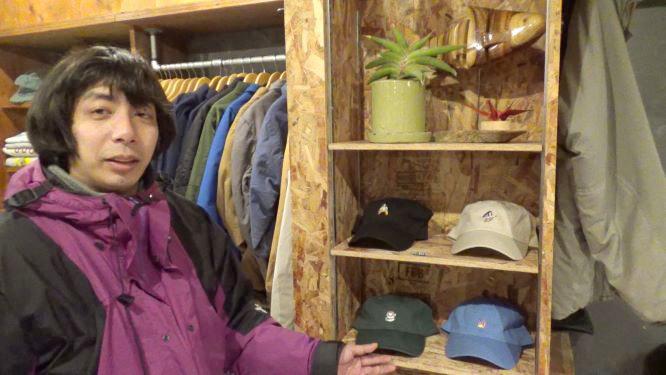 店の棚に色とりどりのキャップを並べる上田 写真提供:MBS