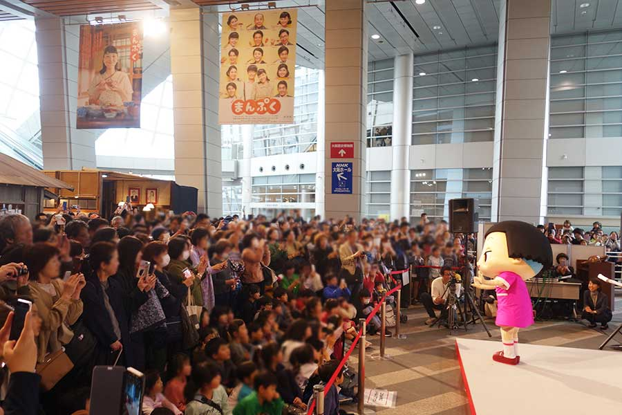 「NHK大阪放送局」のアトリウム。大勢の人々がカメラを手にチコちゃんを撮影