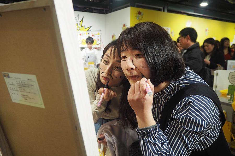 顔ペンで版画メイクを施す女性2人組(24日・大阪市内)