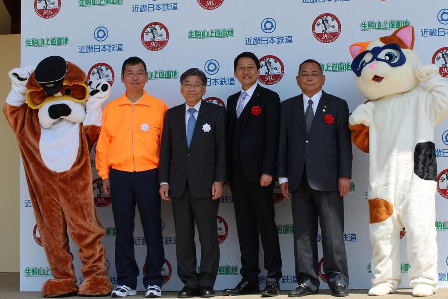 左から遊園地支配人・山田彰彦氏、近畿日本鉄道取締役常務執行役員・西崎一氏、生駒市の小紫雅史市長、市議会議長・中谷尚敬氏。両サイドは、生駒ケーブルキャラクターのブルとミケ