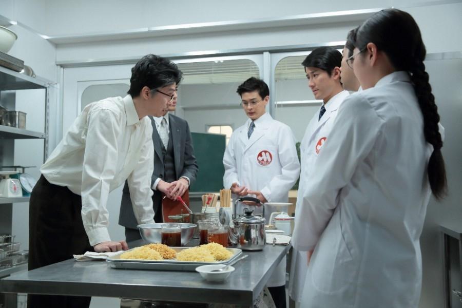 萬平(左・長谷川博己)たちに、新商品のスープを粉末スープにしてはどうかと提案する神部(瀬戸康史)と西野(馬場徹)、久坂(竹村晋太朗)、戸塚(ぎぃ子)ら若手社員たち