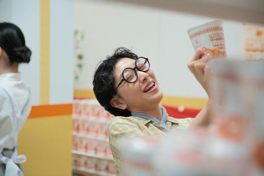「まんぷくヌードル!これ、おいしいのよねぇ!」とほかの客に向けて演技をする福子(安藤サクラ)