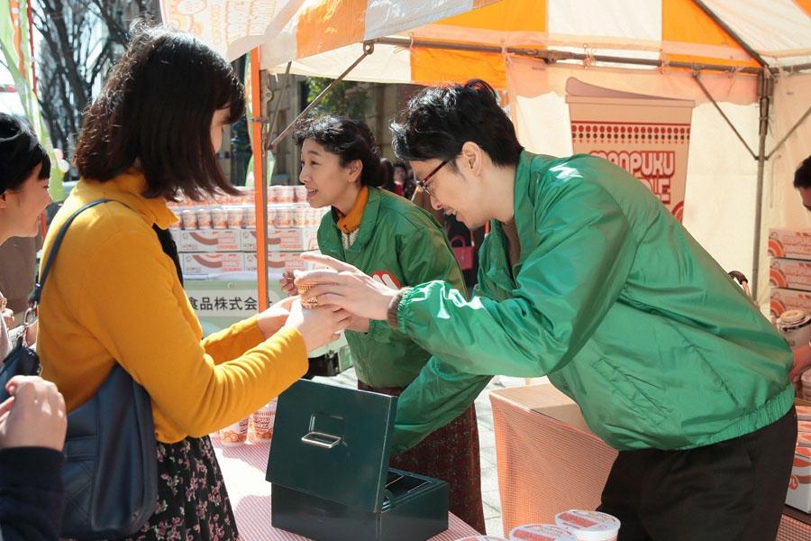 中央通りの歩行者天国で、行列に並ぶ若者たちに次々とまんぷくヌードルを販売する萬平(左・長谷川博己)と福子(安藤サクラ)