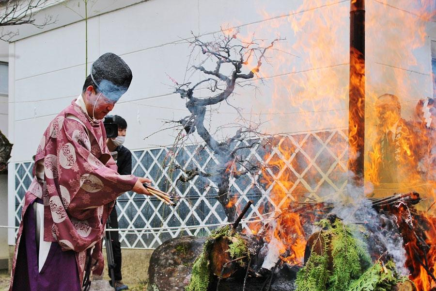 境内の筆塚前で執り行われる「筆供養」で、参拝者が奉納した古筆を炊き上げる禰宜の中村眞一さん