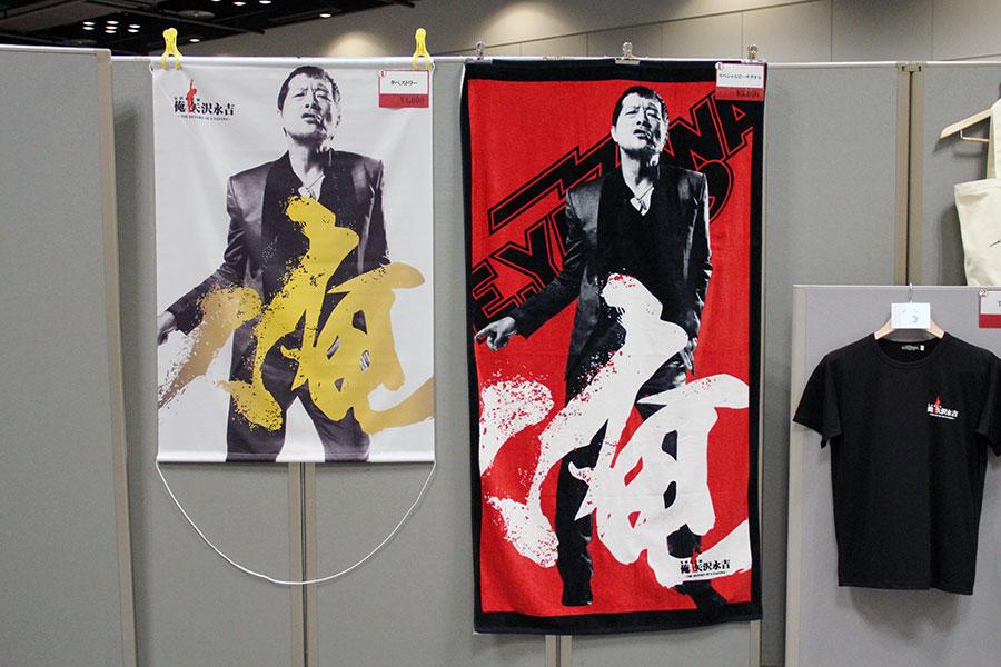 同展示の限定グッズも販売される。タペストリー4000円(左)、スペシャルビーチタオル5000円