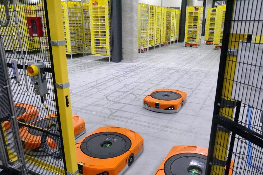 下にもぐって商品の入った黄色い棚を移動させるロボット・ドライブ