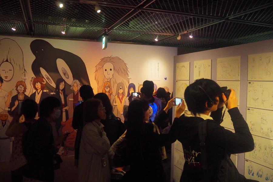 キャラ設定など展示パネルの写真を撮る来場者(24日・大阪市内)