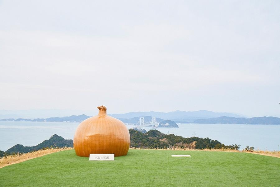 鳴門海峡を見渡す絶景テラスで、巨大な玉ネギと一緒に撮影できる