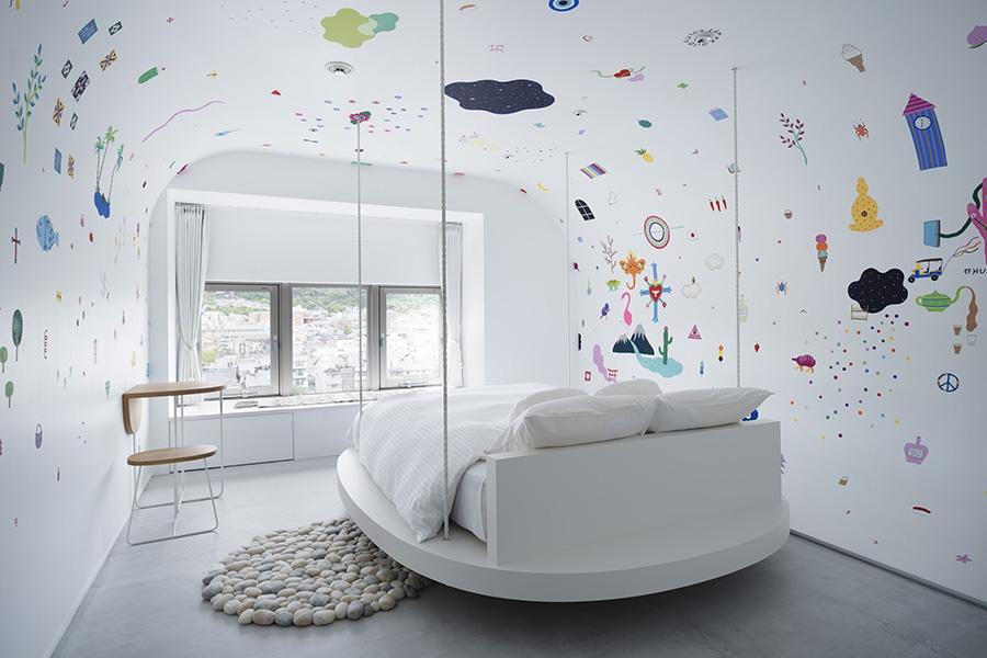 河野ルルの「旅の夢、夢の旅」。天井の角を丸めた壁面にカラフルなペイントが施され、ベッドは4本のワイヤーで天井から吊っている。窓から見える鴨川の景色もいい