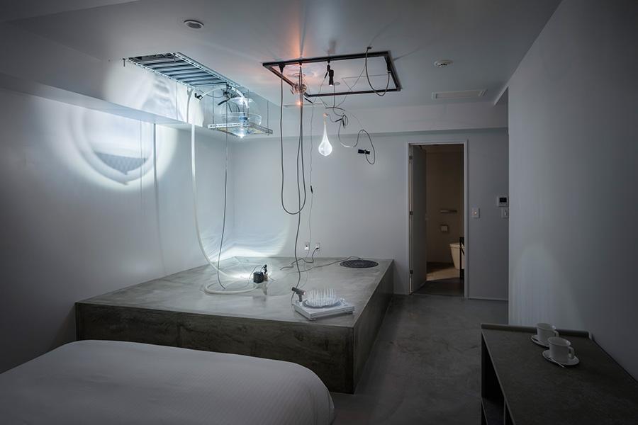 梅田哲也の「no man's waters-place that don't see」。彼らしい水や光を駆使したオブジェが並んでいるが、ホテルの客室としてはとても型破り
