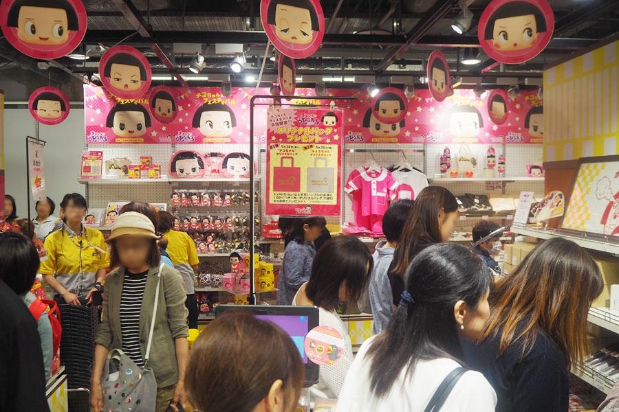 初日は入場整理券が配られ、真剣にチコちゃん商品を選ぶ来場者(24日・大阪市内)