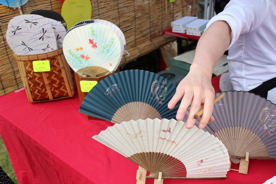 池田匡志さんによる奈良絵扇子。後方には金魚やトンボの図柄の奈良団扇も