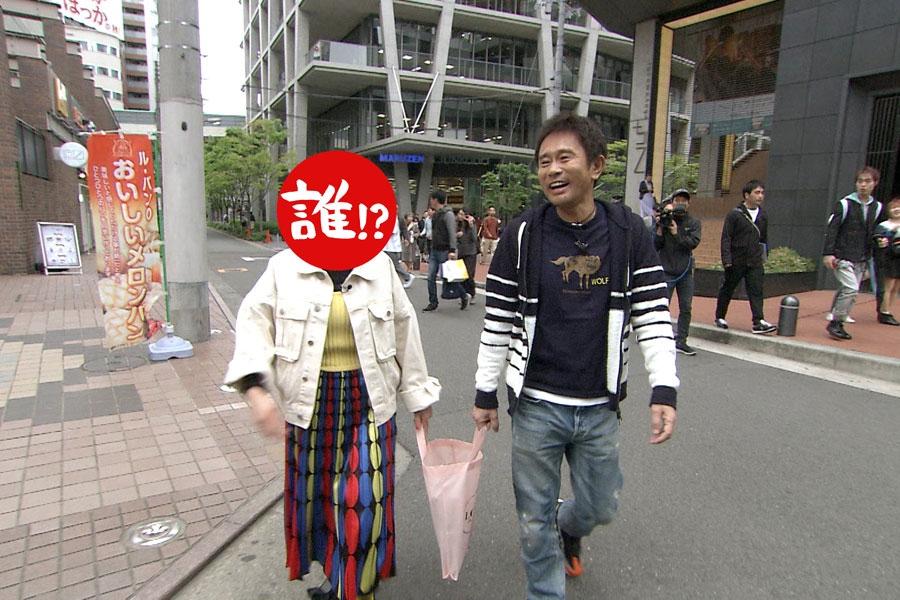結婚情報誌『ゼクシィ』を入れた専用バックを2人で持つというゼクシィ持ちで浜田と街歩きする相方 写真提供:MBS