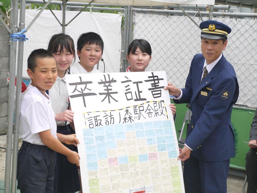 浜寺小学校の生徒らから卒業証書を受け取る横田駅長