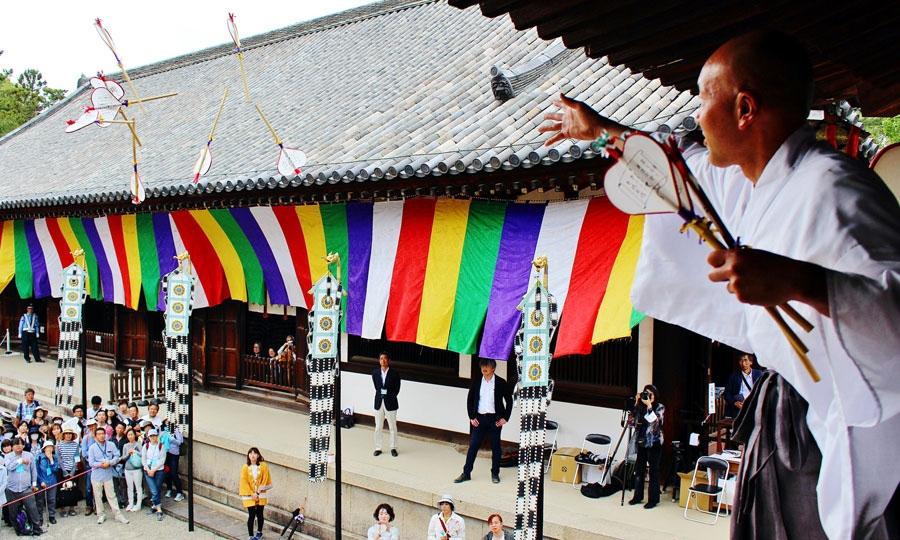 うちわまきの様子。鐘の音にあわせて、計4名の僧侶が鼓楼の2方向から「うちわ」(宝扇)をまく