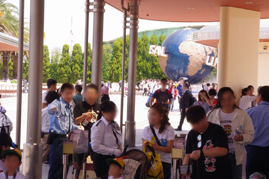「ユニバーサル・スタジオ・ジャパン」の入場ゲートで手荷物検査に協力するゲストら