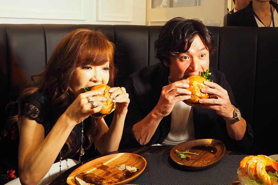 レセプションに登場したハイヒール・モモコ(左)とともに最高級フィレ肉バーガーにかぶりつく大畑大介