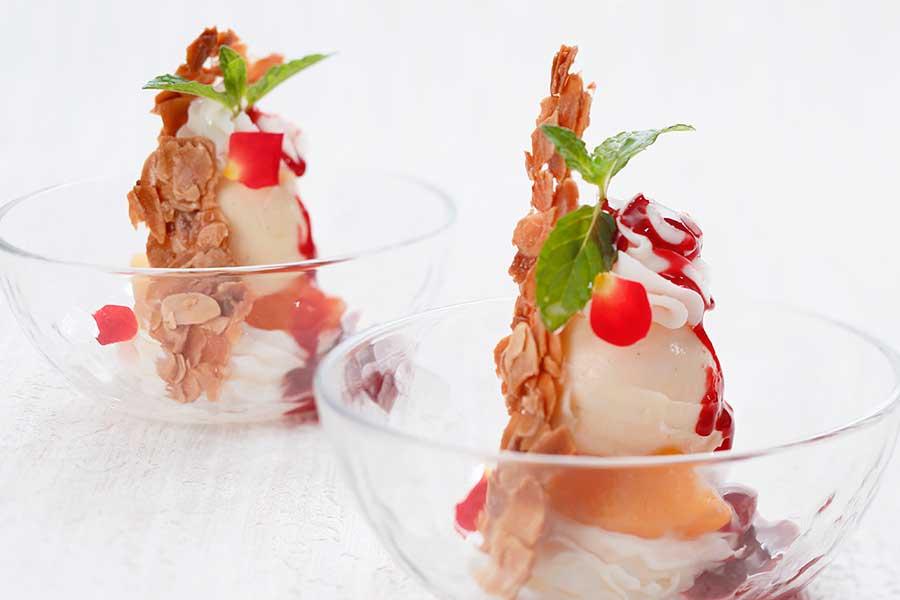 『ライブキッチン』でシェフが手掛ける白桃と黄桃のピーチメルバ。桃のコンポートに、バニラアイス、ベリーのソース、アーモンドキャラリゼとともに