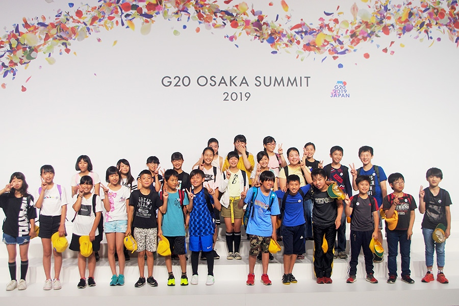 首脳たちが集合写真を撮影した「ファミリーフォト」スペースで撮影する児童たち(2日・大阪市内)