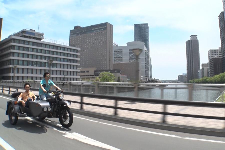 サイドカーに乗って、大阪の街を疾走する浜田雅功と武田真治(写真提供:MBS)