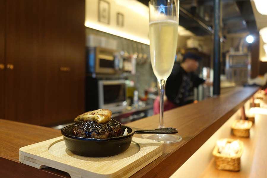 「小皿鉄板酒場 グリル千本」ではスキレット(小さなフライパン)でメニューを提供。写真はフォアグラをトッピングしたトリュフソースのハンバーグ680円。スパークリングなどワインはすべて480円均一