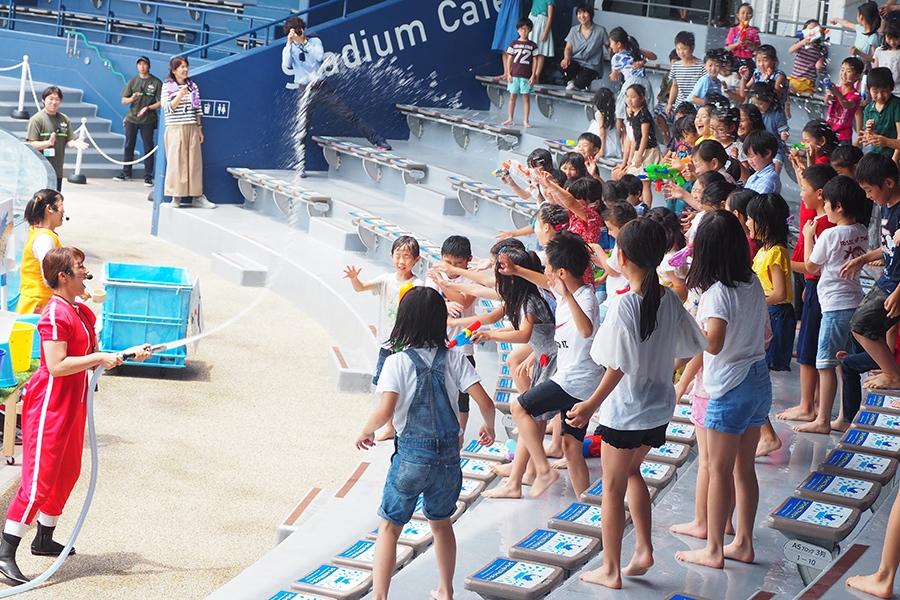 ホースで水を噴出させるパフォーマーに「もっともっと!」「こっちも!」とアピールする子どもたち(10日・京都水族館)