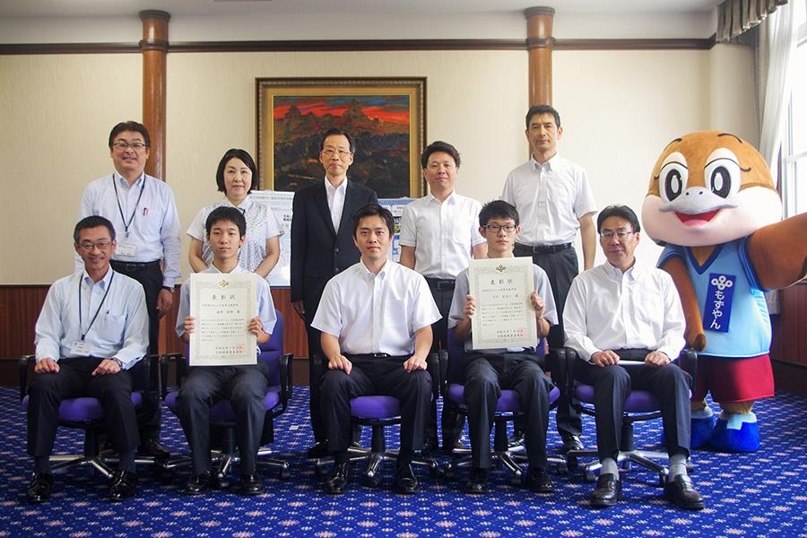 大阪府の吉村洋文知事(中央)と、表彰された汐川空羽人さん(前列右から2番目)、酒井保明さん(前列左から2番目)(10日・大阪府庁)