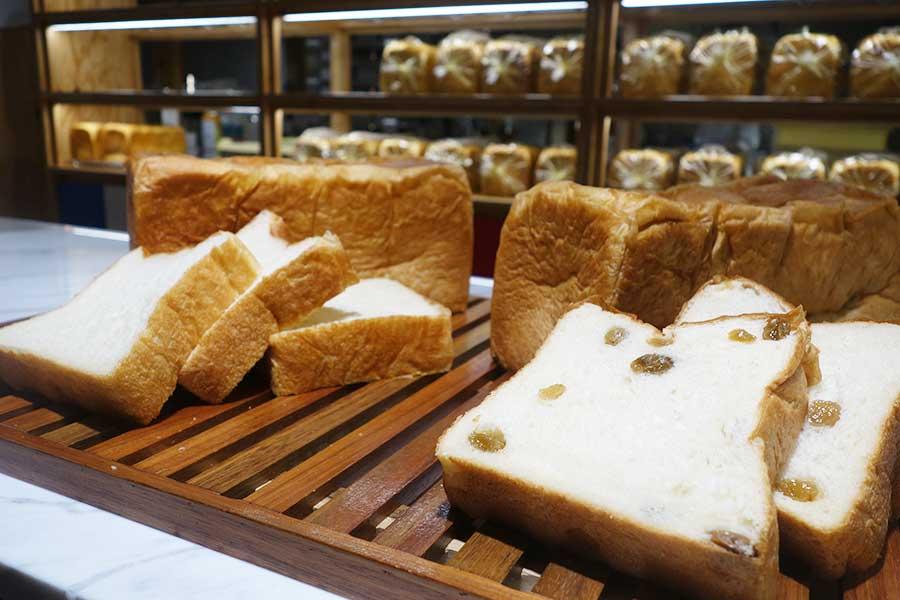 日常遣いというよりも、発酵バターを効かせた「明日が楽しみすぎて」の食パン。「ウキウキがとまらない」(プレーン)800円、「ドキドキなサボタージュ」(レーズン)1480円。以上、2斤の価格・税別)