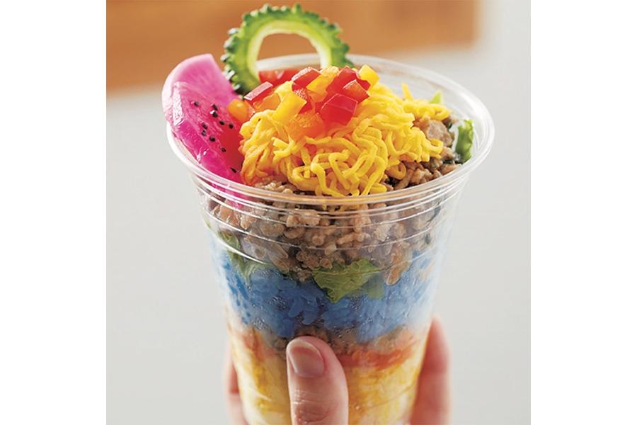 ターメリックライスやゴーヤ、大根のドラゴンフルーツ漬けなど、トロピカルな色彩が印象的な「カップ入りガパオライス」(糀弁当・864円)