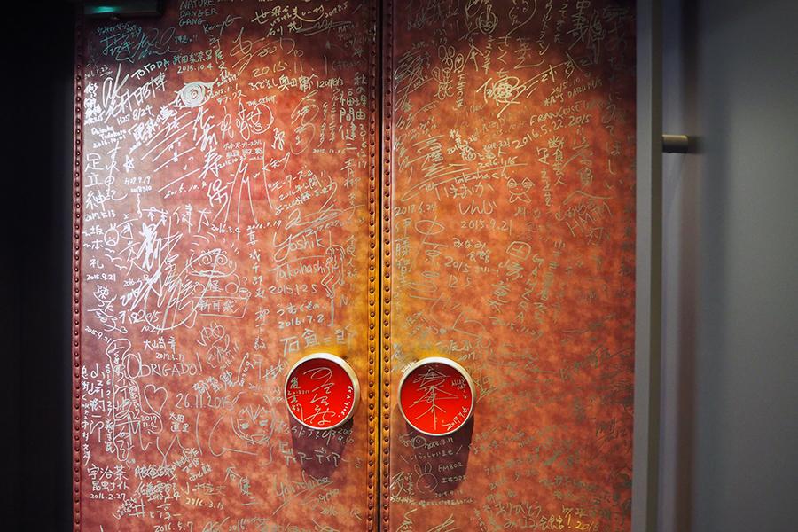 多くの役者や関係者らがサインを残してきた旧「京都みなみ会館」時代の劇場扉も、スクリーン1入口付近に設置