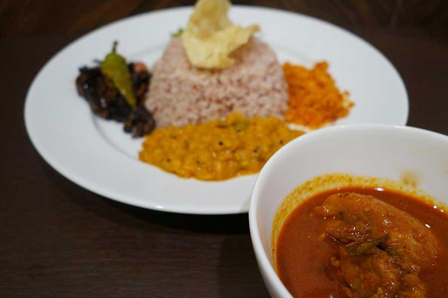 「ククルマス・カリヤ(チキンカレー)」のセット。ご飯の上にはパパダン。途中で細かく割ってふりかけのようにかけて