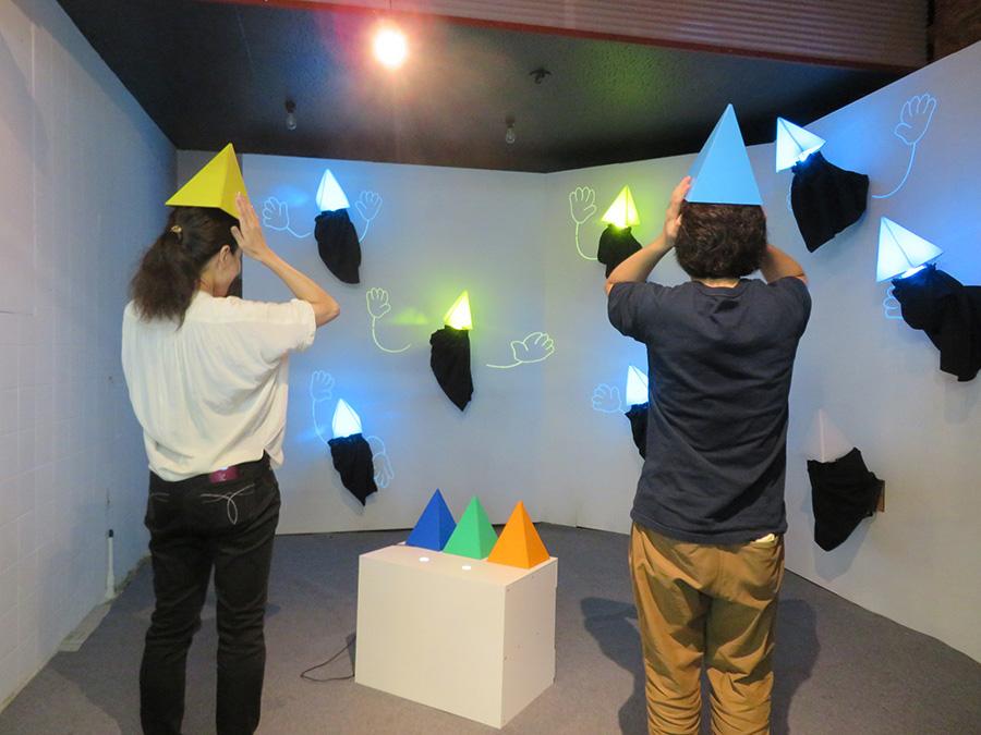 「三和市場」で展示の、本多大和『メイト』。四角すいの帽子をかぶって動くと、壁面のオブジェが発光し、手足(映像)が出てくる