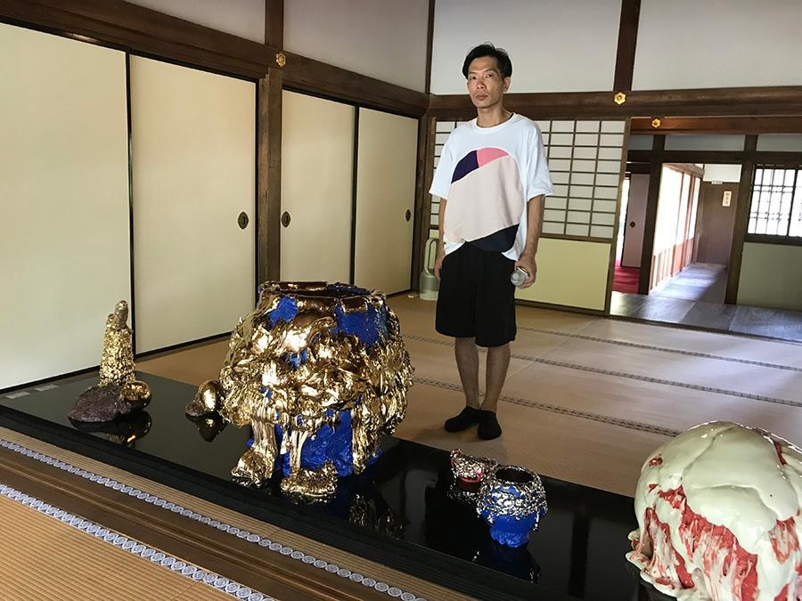 展示作品と桑田卓郎さん。割高台の青い巨大茶碗は、梅花皮状の部分に釉薬を数10キロ使用した迫力ある作品