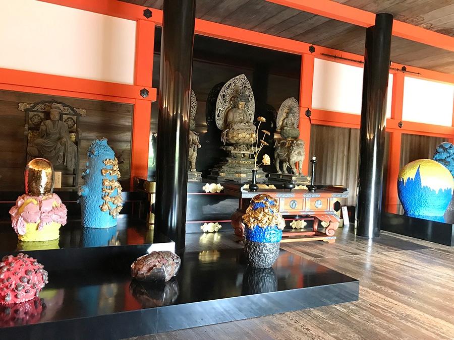 重要文化財である経堂では、最大1.6メートルの巨大オブジェ群が釈迦三尊像と並び立つ
