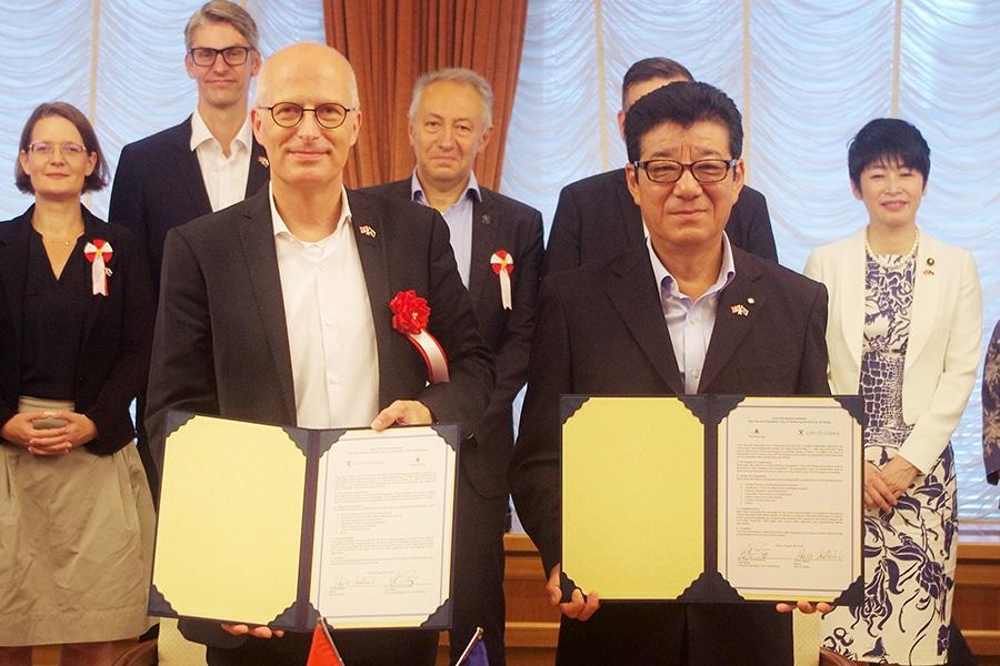 姉妹(友好)都市提携30周年共同宣言(案)に署名した大阪市の松井一郎市長(右)とハンブルク市のピーター・チャンチャー市長(28日・大阪市役所)
