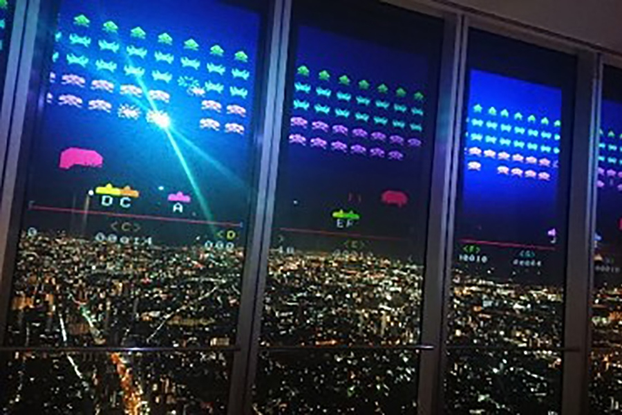 街を見下ろすビル外周ガラス面に「インベーダーゲーム」の画面を投影