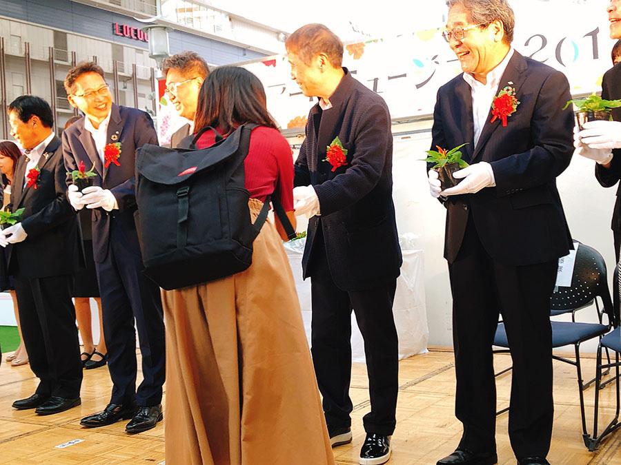 お花のポットをプレゼントされる来場者(27日・大阪市内)