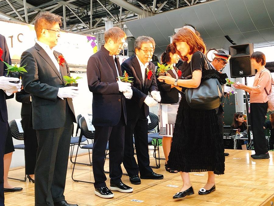 大阪府副知事や安藤忠雄さんらが、来場者にお花をプレゼントした(27日・大阪市内)