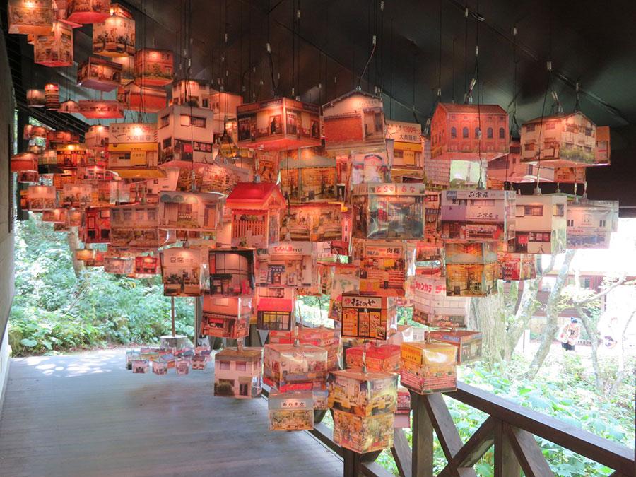 「六甲高山植物園」内の映像館で展示される、栗真由美の作品。阪神尼崎駅周辺の商店を撮影した画像によるランタンが大量に吊られている