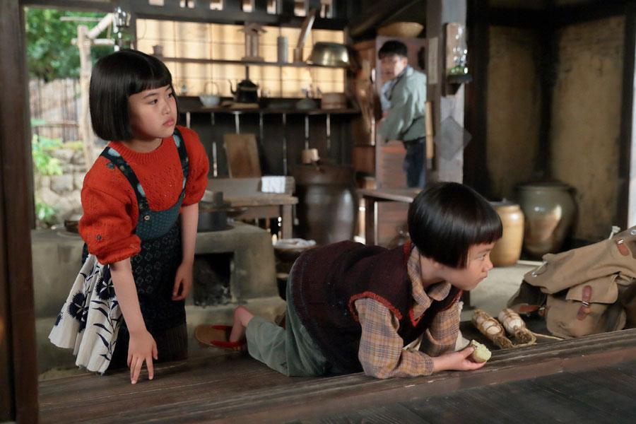 縁側に誰かいると気づき、川原家の台所からのぞき込む喜美子(川島夕空)と直子(やくわなつみ)
