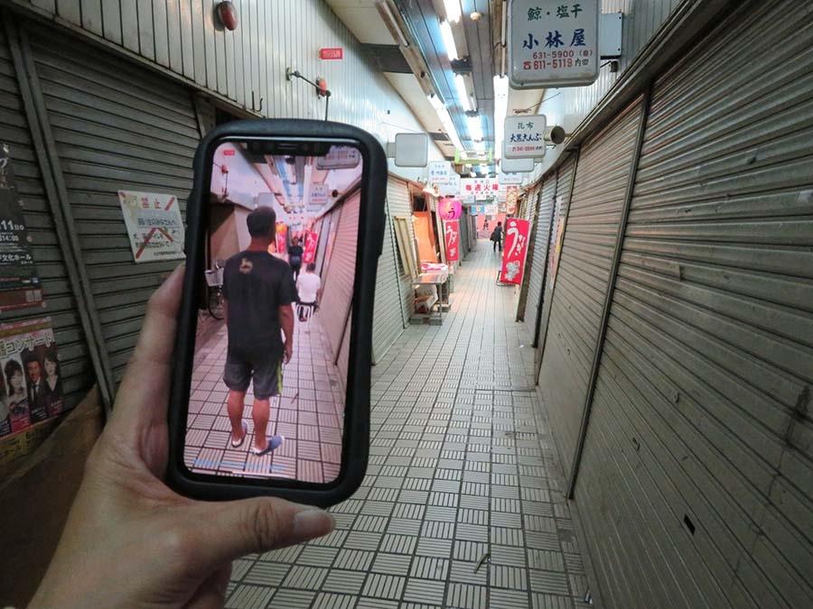丸五市場《死にゆくこと、生きながらえること》 商店街でスマホをかざすと、現実にはいない人たちの姿が画面に。別会場で高精細3Dスキャン撮影された人たちが出現(作品を鑑賞するにはアプリダウンロードが必要・第12留)