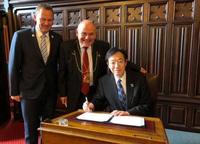 WECP加盟書類にサインする久元市長。タータンチェックの本場イギリスで「神戸タータン」をネクタイでアピールしている(提供:神戸市)